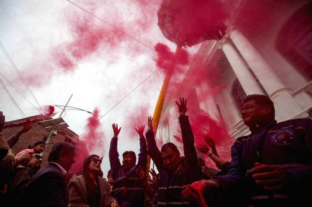 """KATHMANDU, March 14, 2019 - Nepalese devotees throw vermilion powder after hoisting a ceremonial bamboo pole known as """"chir"""" in celebration of the Holi Festival at Basantapur Durbar Square ..."""