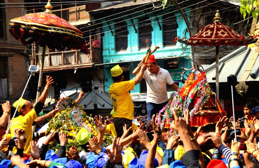 Priests exchange holy lamps during the chariot festival at Ason in Kathmandu, Nepal, March 21, 2015. The chariots of Kankeshwori, Bhadrakali and Sankata were ...