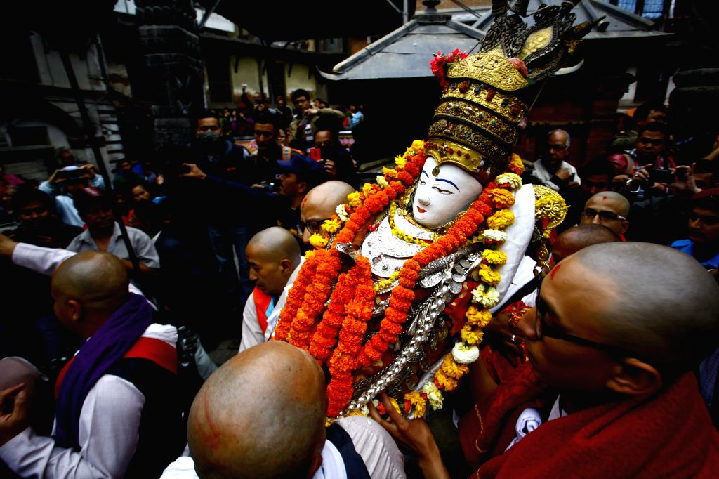 People carry an idol of Seto Machhendranath from a temple to a chariot during a procession to mark the beginning of Seto Machhindranath Chariot festival in ...