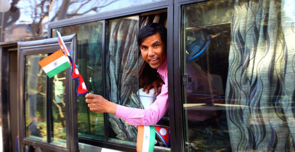 A passenger cheers on a bus proceeding to Banaras during the inauguration of Kathmandu-Banaras bus service in Kathmandu, Nepal, March 5, 2015. The bus service ...