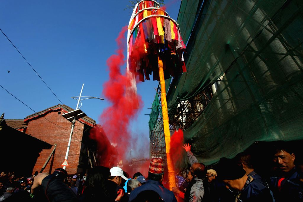 """KATHMANDU, March 5, 2017 - Nepalese people play with colored powders after hoisting a colorful pole known as """"chir"""" to mark the beginning of the week-long Holi festival in Kathmandu, Nepal, ..."""