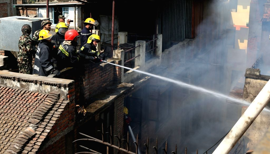 KATHMANDU, March 7, 2019 - Fire fighters work to extinguish fire at a house near the Hanumandhoka Durbar Square in Kathmandu, Nepal, March 7, 2019. Three were injured in a fire which broke out ...