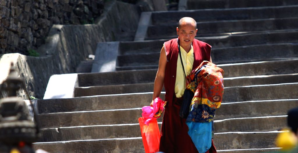 A Buddhist monk brings his belongings from a damaged monastery after a massive earthquake in Kathmandu, Nepal, May 2, 2015. The death toll from last Saturday's ...