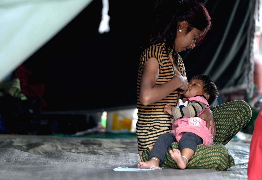A woman feeds a baby in Kathmandu, Nepal, on May 2, 2015. The death toll from last Saturday's powerful earthquake in Nepal reached 6,659 and a total of 14,062 ...