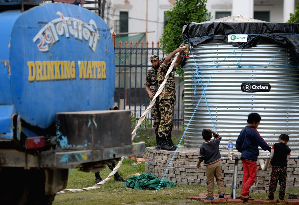 Soldiers fill fresh water in barrels in Kathmandu, Nepal, on May 2, 2015. The death toll from last Saturday's powerful earthquake in Nepal reached 6,659 and a total ...