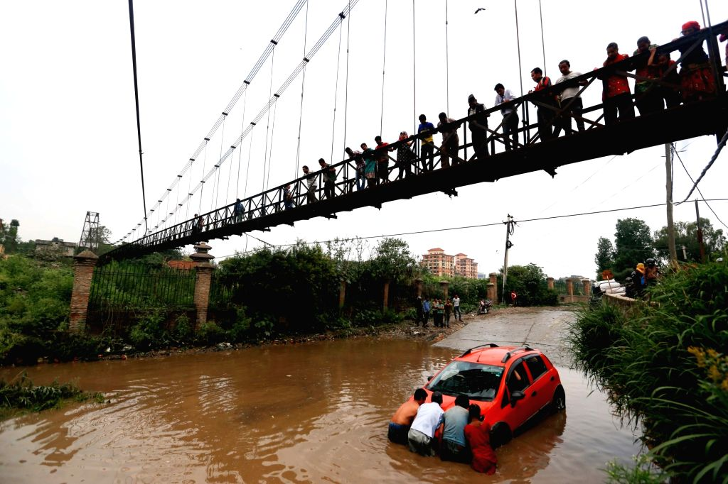 KATHMANDU, May 31, 2018 - Locals try to pull out a car stuck in water-logged street due to heavy rainfall at Sanepa in Lalitpur, Nepal on May 31, 2018. People in Kathmandu have witnessed pre-monsoon ...