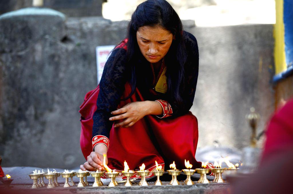 """A devotee lights ghee lamps to mark Buddha Jayanti festival in Kathmandu, Nepal, May 4, 2015. Buddha Jayanti, sometimes informally called """"Buddha's ..."""
