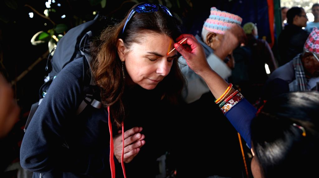 KATHMANDU, Nov. 1, 2016 - A Tourist receives colourful 'Tika' on the forehead during Bhai Tika, the fifth and last day of Tihar festival, at Yamleshwor temple which is under reconstruction, in ...