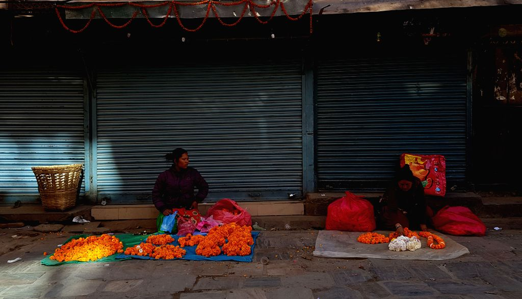KATHMANDU, Nov. 13, 2016 - Local vendors sell flowers in front of closed shops at a market during a general strike called by Netra Bikram Chand-led CPN (Maoist) in Kathmandu, Nepal, Nov. 13, 2016. ...
