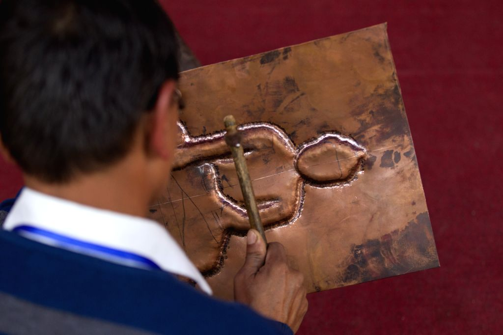KATHMANDU, Nov. 26, 2016 - A man drafts the pattern of a Buddha on a copper plate during the 14th Handicraft Trade Fair and 12th Craft competition at Bhrikutimandap, Kathmandu, capital of Nepal, Nov. ...
