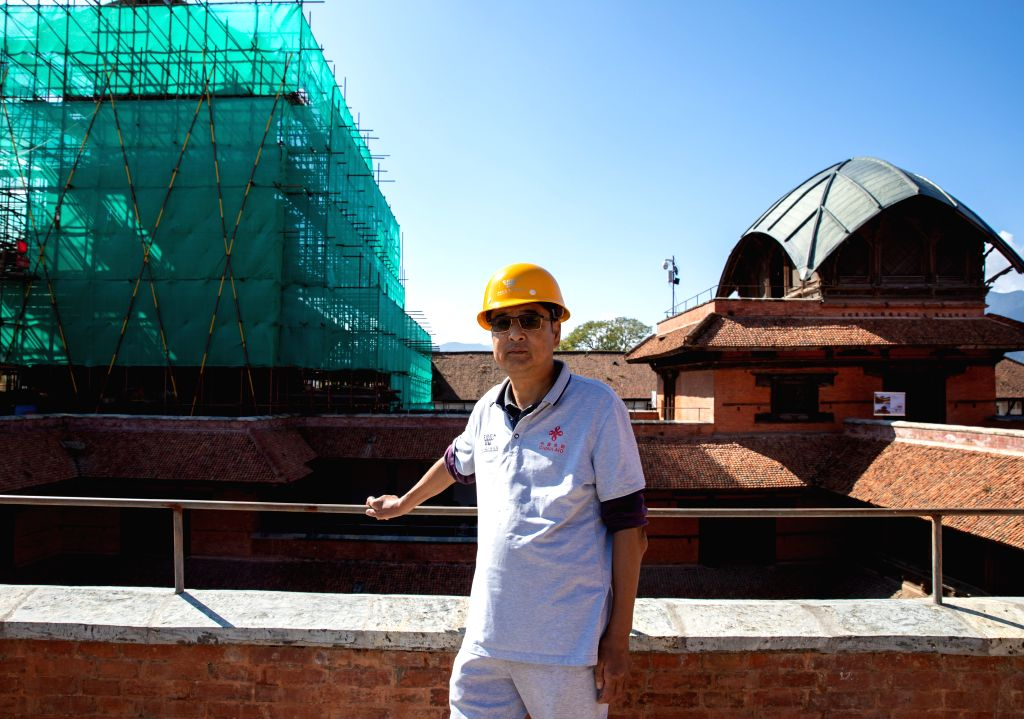 KATHMANDU, Oct. 11, 2019 - Zhou Jianguo, the technical chief of the Chinese restoration team, poses for photos at the restoration site of the nine-storeyed Basantapur complex in Kathmandu, Nepal, on ...