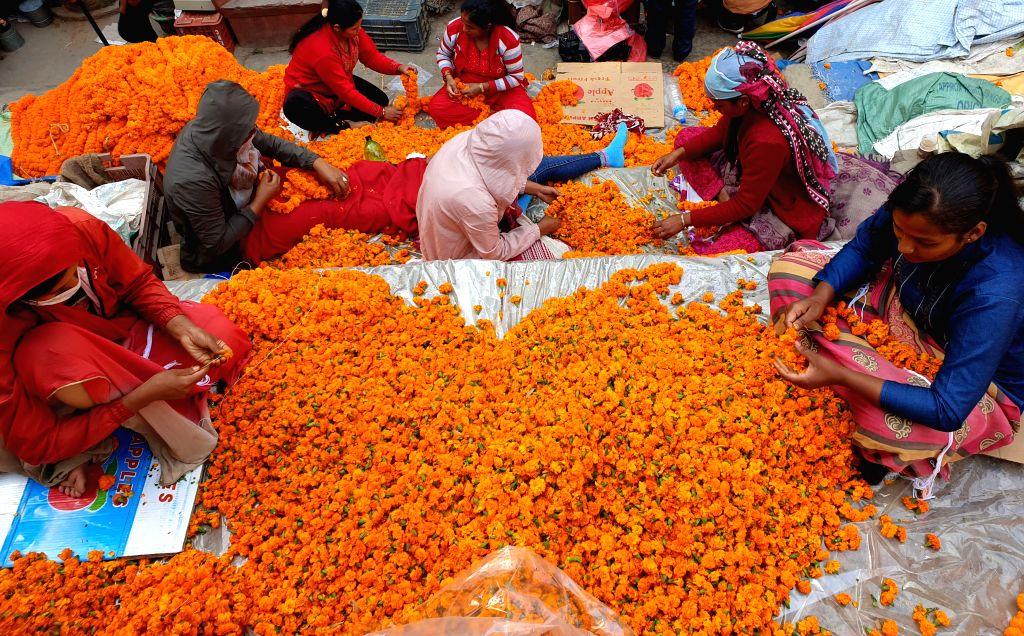 KATHMANDU, Oct. 27, 2019 - Nepalese women prepare garlands of marigold flowers for Tihar festival at a market in Kathmandu, Nepal, Oct. 26, 2019.