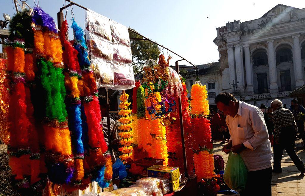 KATHMANDU, Oct. 28, 2016 - A man buys decorative flower garlands for Tihar festival at Hanuman Dhoka Durbar Square in Kathmandu, Nepal, Oct. 28, 2016.