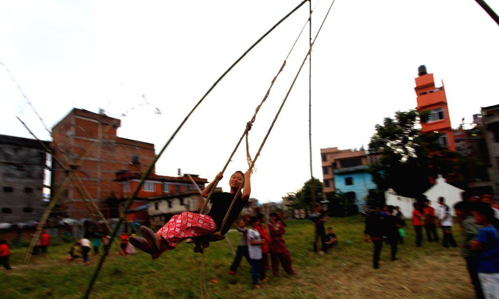 KATHMANDU, Oct. 8, 2016 - A Nepali girl enjoys a ride on a traditional Dashain swing in celebration of the Dashain festival in Kathmandu, Nepal, Oct. 7, 2016. Hindus in Nepal celebrate Dashain as ...