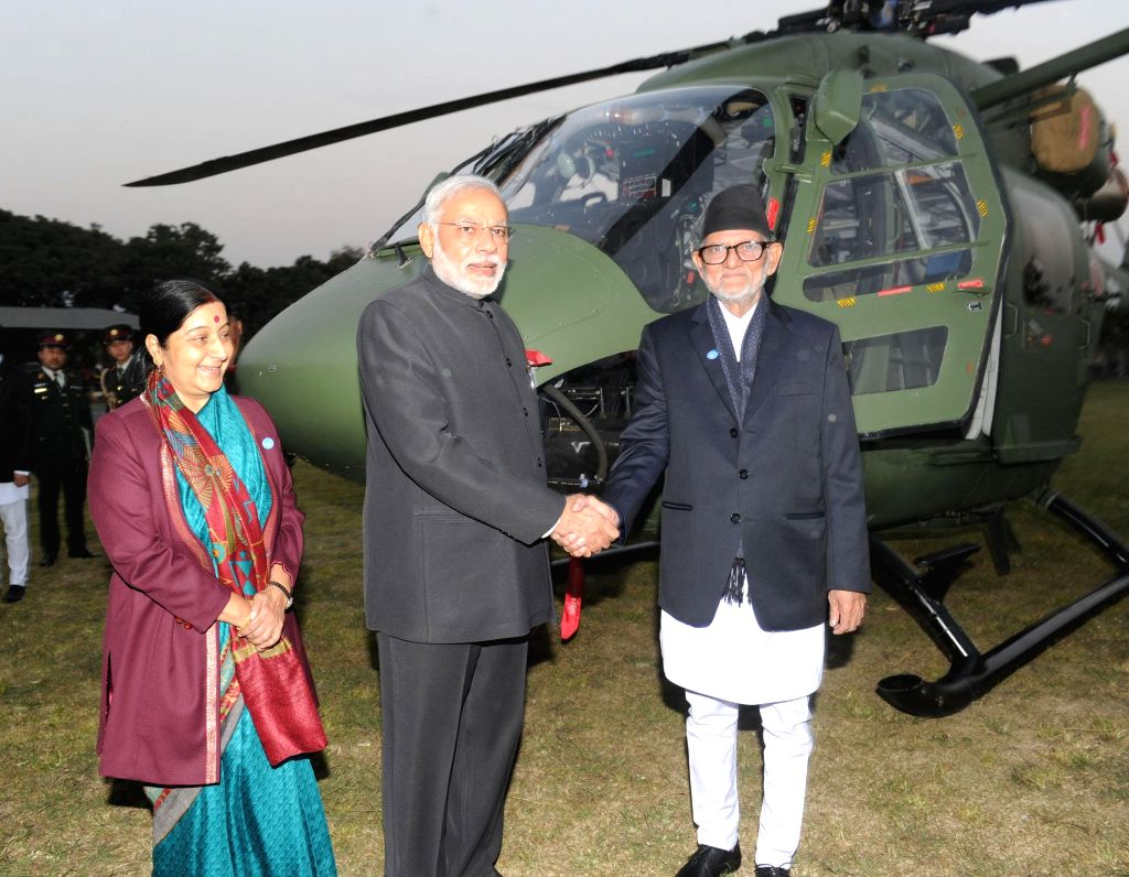 Prime Minister Narendra Modi hands over the Dhruv ALH to the Prime Minister of Nepal, Sushil Koirala, at Army Pavilion, in Kathmandu, Nepal, on Nov 25, 2014. Also seen  Union Minister for . - Narendra Modi and Sushma Swaraj