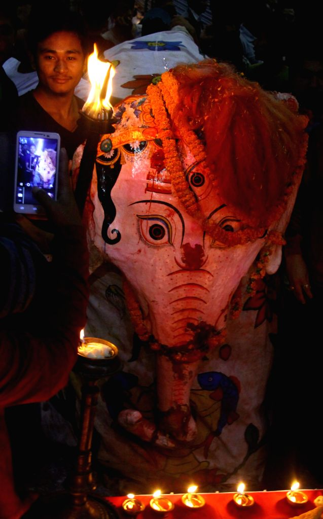 A young Nepalese takes a photo of Pulukisi, or elephant-masked performer, in the evening of the 6th day of the Indrajatra Festival at Newroad in Kathmandu, ...