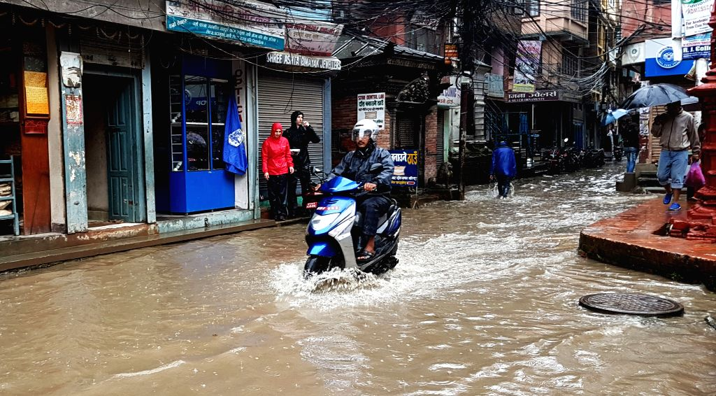 KATHMANDU, Sept. 12, 2016 - A motorbike rider crosses a flooded street in Kathmandu, Nepal, Sept. 12, 2016. Heavy rainfall have affected capital Kathmandu and many other cities in the country.