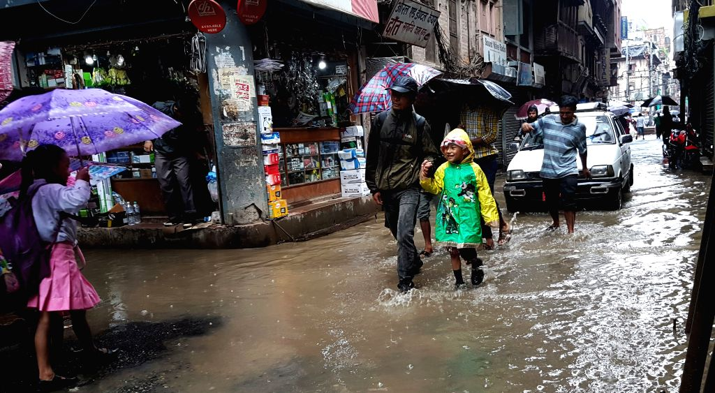 KATHMANDU, Sept. 12, 2016 - People walk on a flooded street in Kathmandu, Nepal, Sept. 12, 2016. Heavy rainfall have affected capital Kathmandu and many other cities in the country.