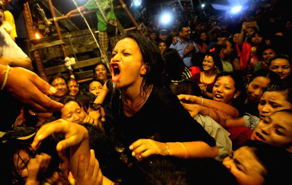 KATHMANDU, Sept. 18, 2016 - Nepalese women struggle to drink homemade alcohol during celebrations of the Indrajatra festival at Hanumandhoka Durbar Square in Kathmandu, Nepal, Sept. 17, 2016. ...