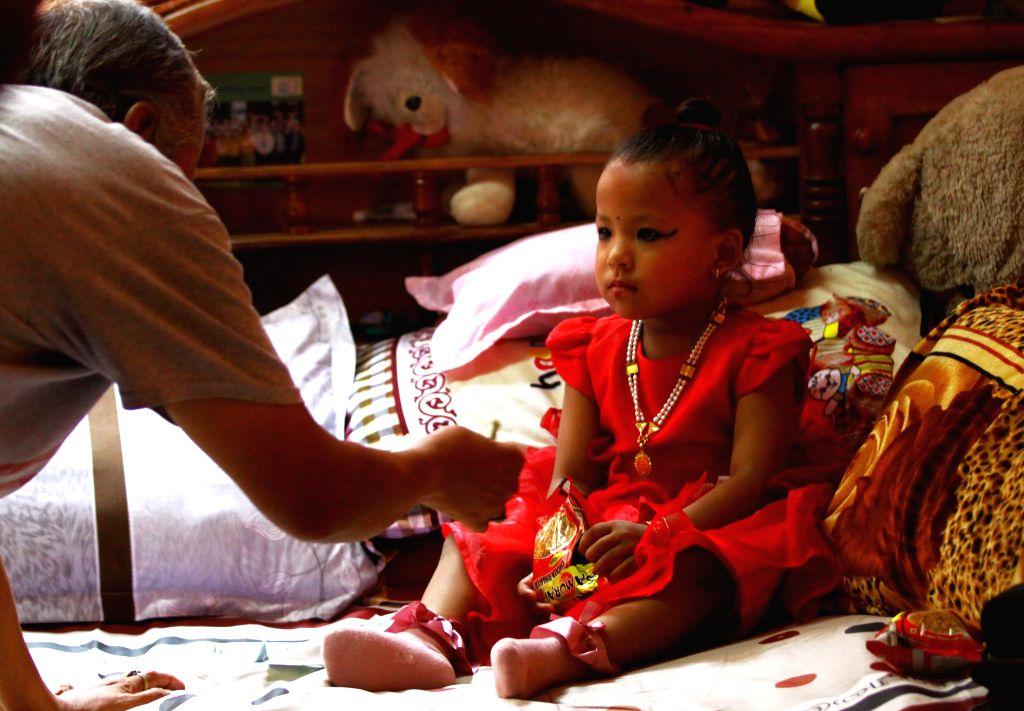 KATHMANDU, Sept. 28, 2017 - A devotee offers prayers to Nepal's newly appointed Living Goddess Kumari, Trishna Shakya, at her home before she formally takes her Kumari House in Kathmandu, Nepal, ...