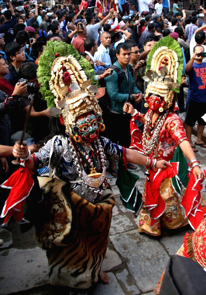 "Masked dancers perform during the erection of the wooden pole ""Indradhwoj"" at Hanumandhoka Durbar Square to mark the beginning of Indrajatra Festival in"