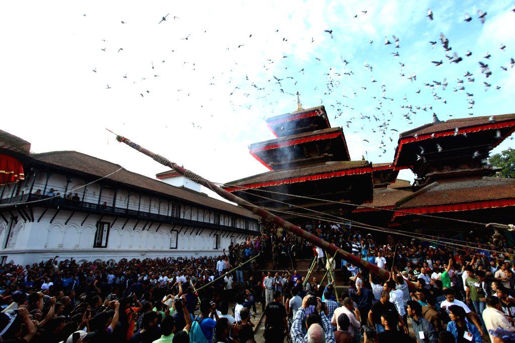 "Nepalese people erect a wooden pole ""Indradhwoj"" at Hanumandhoka Durbar Square to mark the beginning of Indrajatra Festival in Kathmandu, Nepal, Sept. .."