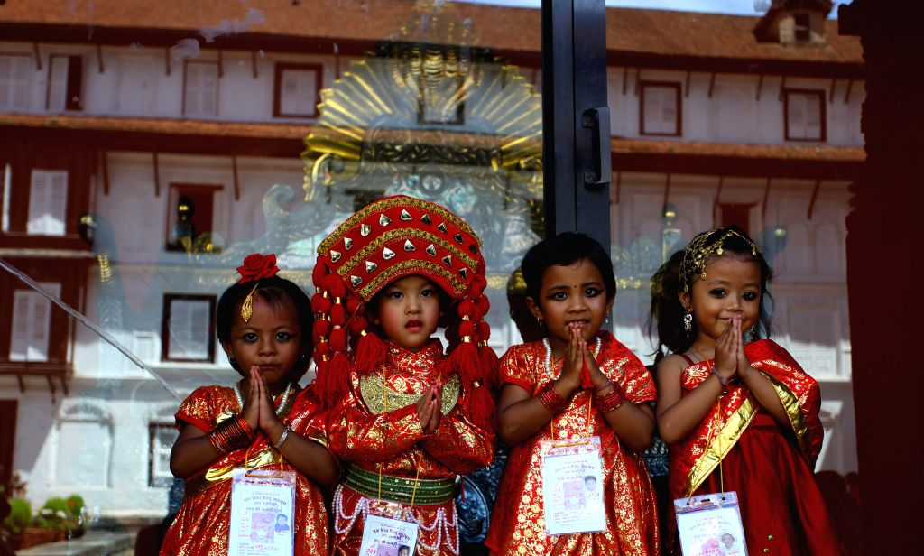 Little girls dressed up as living Goddess react during the procession of Kumari Puja organized on the occasion of Indrajatra festival at Hanumandhoka in ...