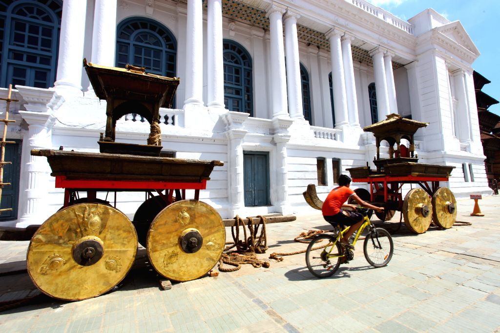 A bicycle rider passes by the newly plated wheels of Ganesh and Bhairav chariots for Indrajatra Festival at Hanumandhoka Durbar Square in Kathmandu, Nepal, on ...