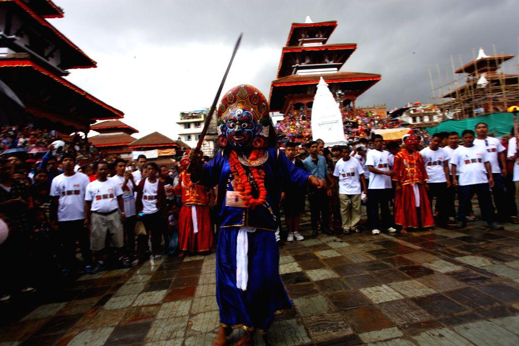 A maksed dancer named Sawabhaku performs dance during the Indrajatra festival at Hanumandhoka Durbar Square in Kathmandu, Nepal, Sept. 8, 2014. Nepalese celebrate