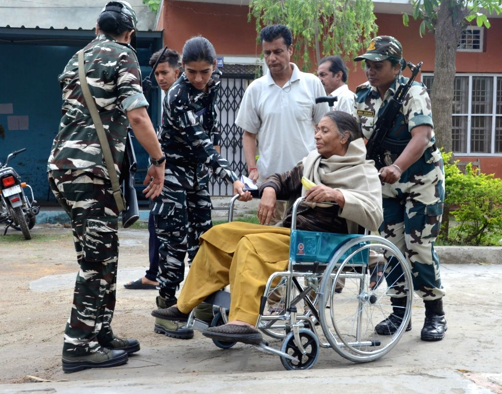 Kathua: A wheelchair-bound woman being assisted to a polling station by women security personnel to cast her vote for the second phase of 2019 Lok Sabha elections, in Jammu and Kashmir's Kathua, on April 18, 2019. (Photo: IANS)