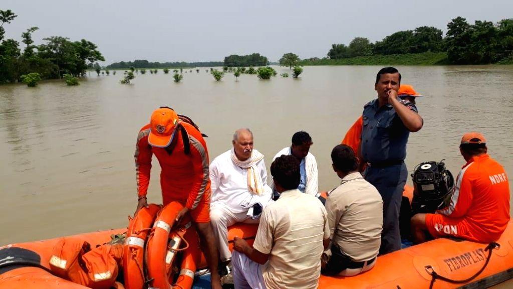 Katihar: NDRF personnel conduct evacuation drive in the flood-hit Katihar of Bihar, on July 17, 2019. (Photo: IANS)