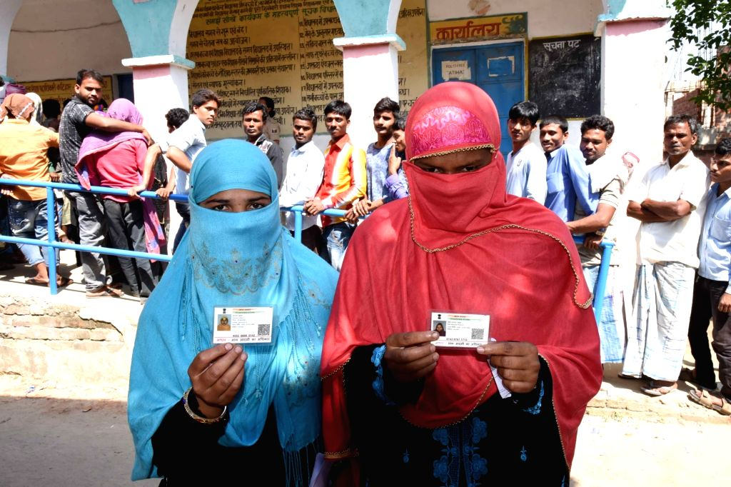 Katihar: Women show their Aadhaar cards as they arrive to cast their votes for the second phase of 2019 Lok Sabha elections in Bihar's Katihar, on April 18, 2019. (Photo: IANS)