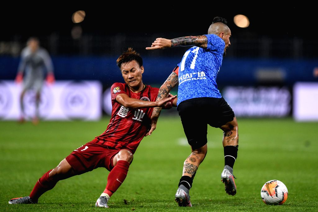 Ke Zhao (L) of Henan Jianye FC vies with Marek Hamsik of Dalian Yifang FC during the second round match between Dalian Yifang FC and Henan Jianye FC at the postponed ...