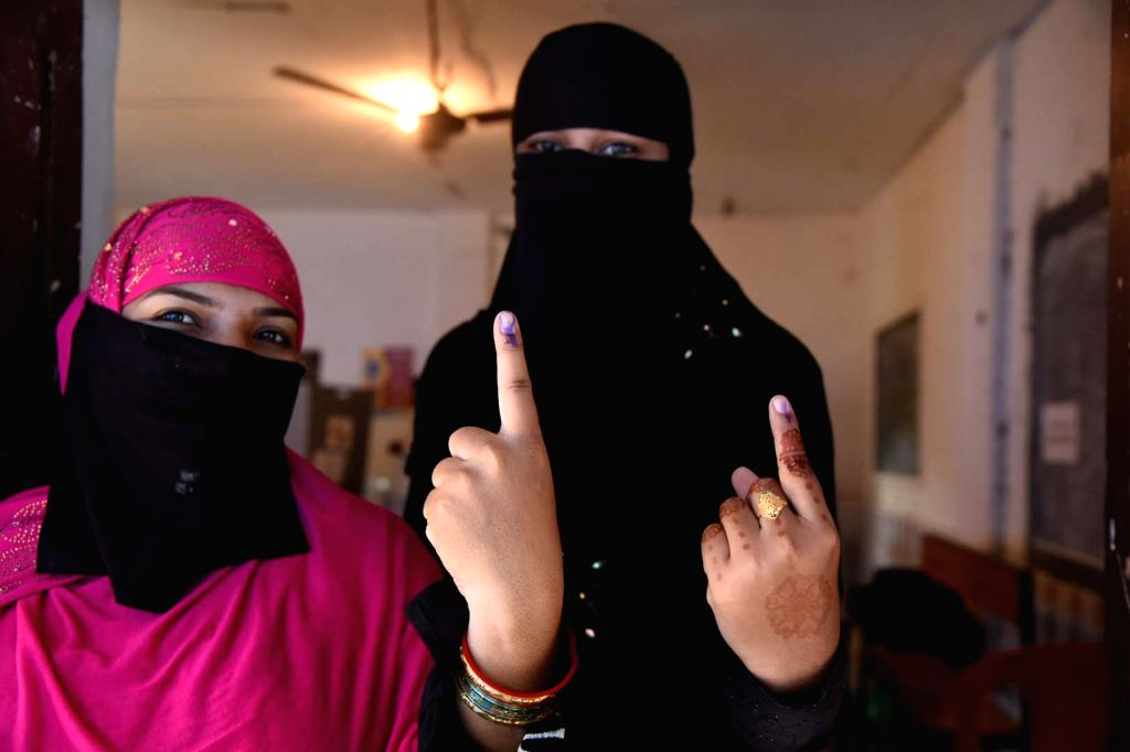 Kendrapara (Odisha): Burqa-clad women show their forefingers marked with indelible ink after casting their vote during the fourth phase of 2019 Lok Sabha elections in Odisha's Kendrapara on April 29, ...