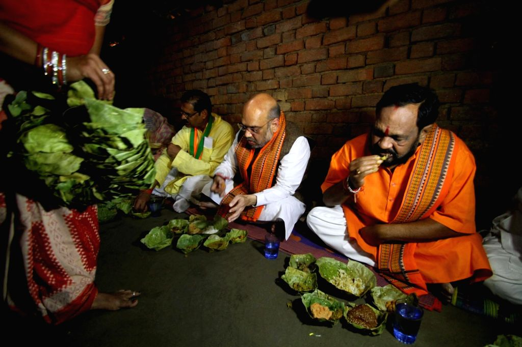 :Kendujhar: BJP President Amit Shah haves lunch at the Dalit daily wager's house in Deogaon village at Kendujhar District of Odisha on April 5, 2018. Also seen BJP Odisha president Basanta ...