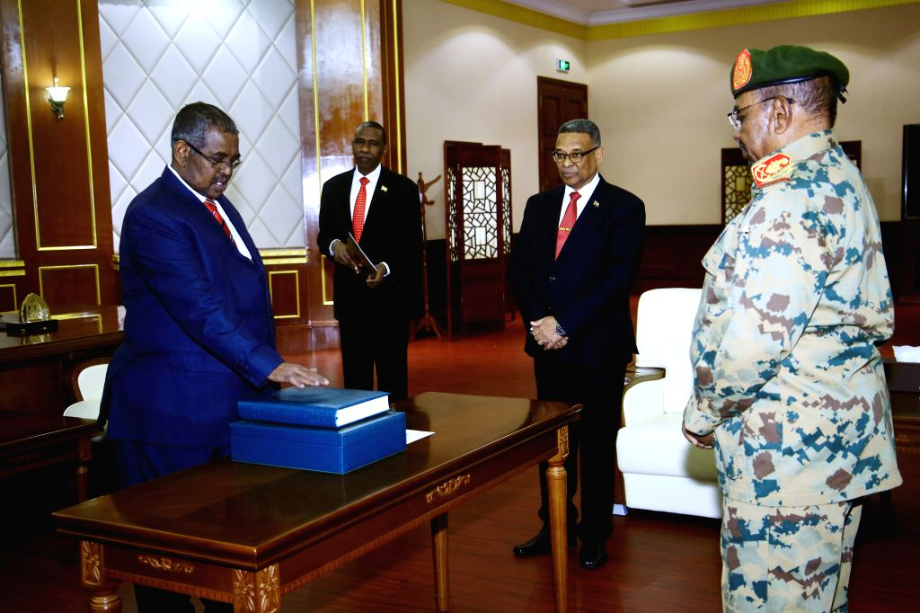 KHARTOUM, Feb. 24, 2019 - Newly-appointed Sudanese prime minister Mohamed Tahir Ayala (L) takes the constitutional oath at the presence of Sudanese President Omar al-Bashir (1st R) at Presidential ... - Mohamed Tahir Ayala