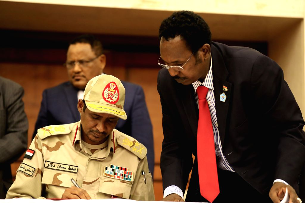 KHARTOUM, July 17, 2019 - Mohamed Hamdan Daqlu (L), deputy chairman of Sudan's Transitional Military Council, signs on the Political Declaration with the Freedom and Change Alliance in Khartoum, ...