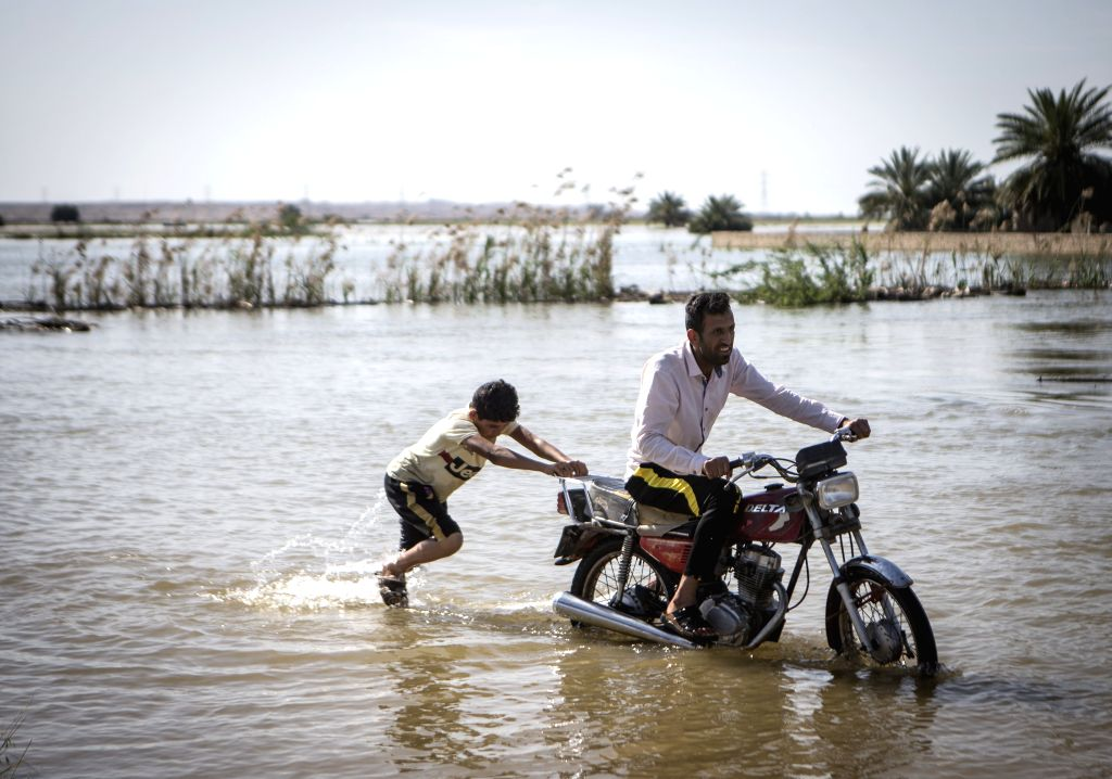 KHUZESTAN, April 9, 2019 - A kid helps a man ride a motorcycle through flood water at a village in Khuzestan province, southwestern Iran, April 8, 2019. The unprecedented floods across Iran over the ...