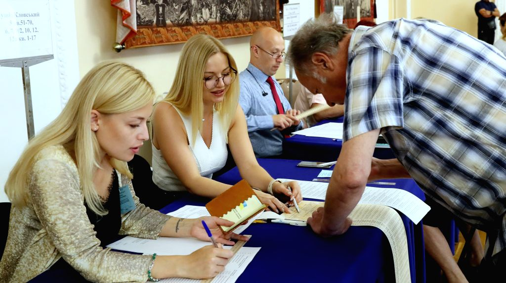 KIEV, July 21, 2019 - Electoral workers help a voter with his ballot at a polling station in Kiev, Ukraine, July 21, 2019. Ukraine held snap parliamentary elections on Sunday. The elections were ...