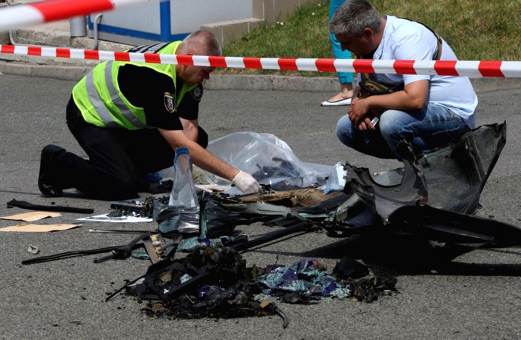 KIEV, June 27, 2017 - Investigators inspect the site of car blast in Kiev, capital of Ukraine, June 27, 2017. A senior Ukrainian intelligence officer was killed on Tuesday in a car blast in the ...