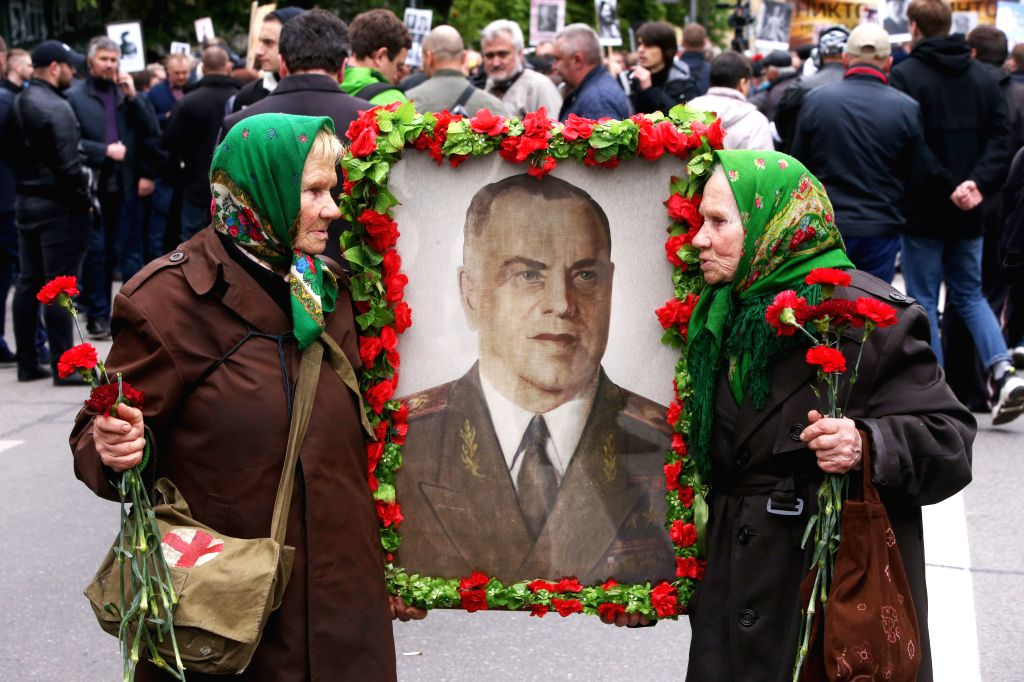 KIEV, May 10, 2019 - Two women hold a portrait of their father who died in World War II as they attend a parade commemorating the 74th anniversary of the victory over Nazism during World War II in ...