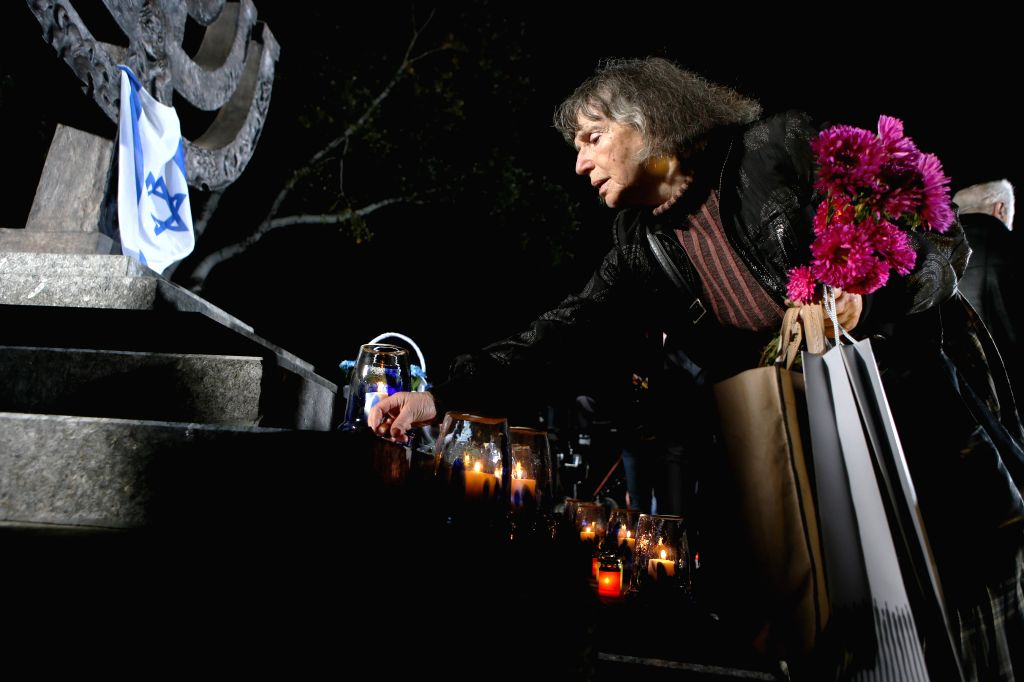 KIEV, Sept. 30, 2016 - A woman lays a candle in front of a monument during a ceremony commemorating the massacre of about 150,000 Nazi victims in Babi Yar near Kiev from 1941 to 1943, in Kiev, ...