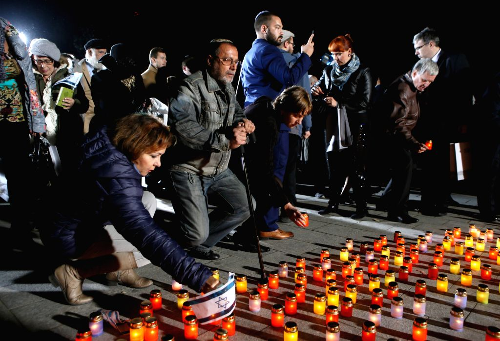KIEV, Sept. 30, 2016 - People lay candles in front of a monument during a ceremony commemorating the massacre of about 150,000 Nazi victims in Babi Yar near Kiev from 1941 to 1943, in Kiev, Ukraine, ...