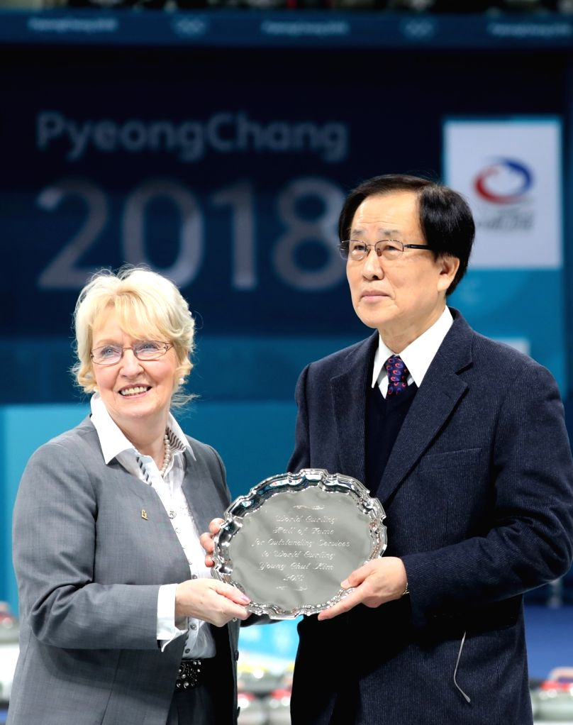 Kim Young-cheol (R), adviser to the Korean Curling Federation, accepts a plaque from Kate Caithness, president of the World Curling Federation, at Gangneung Curling Center in Gangneung, ...