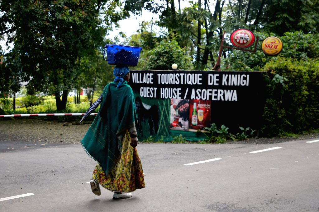 KINIGI (RWANDA), Oct. 7, 2019 A woman walks past the signpost of a guest house in Kinigi sector of Musanze District, northern Rwanda, on Oct. 7, 2019. Rwandan police said the situation ...