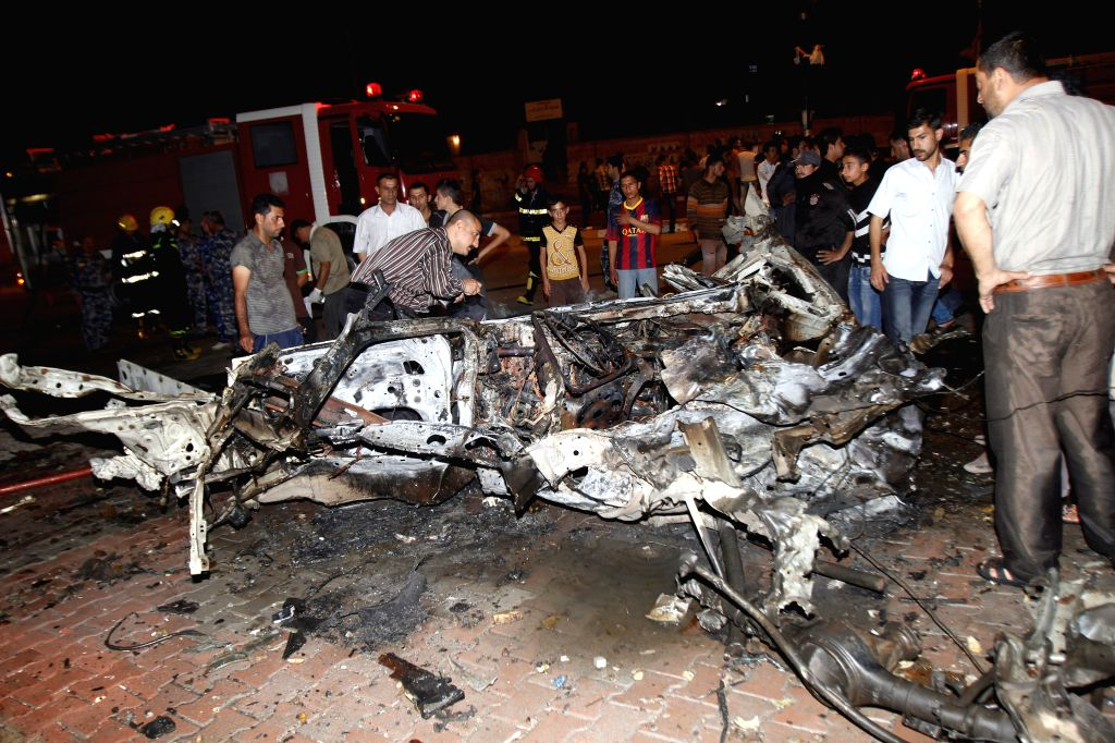People inspect the site of a car bomb attack in the northern Iraqi city of Kirkuk April 24, 2014. A total of 25 people were killed and 35 others wounded in separate
