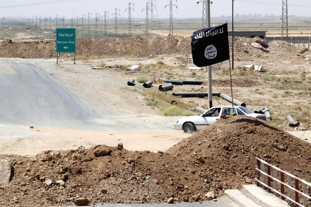 """A flag of Islamic State is seen on the """"border"""" of the Islamic State militants and Kurdish fighters on the road to Tikrit in Kirkuk, Iraq, Aug. 23, 2014. .."""