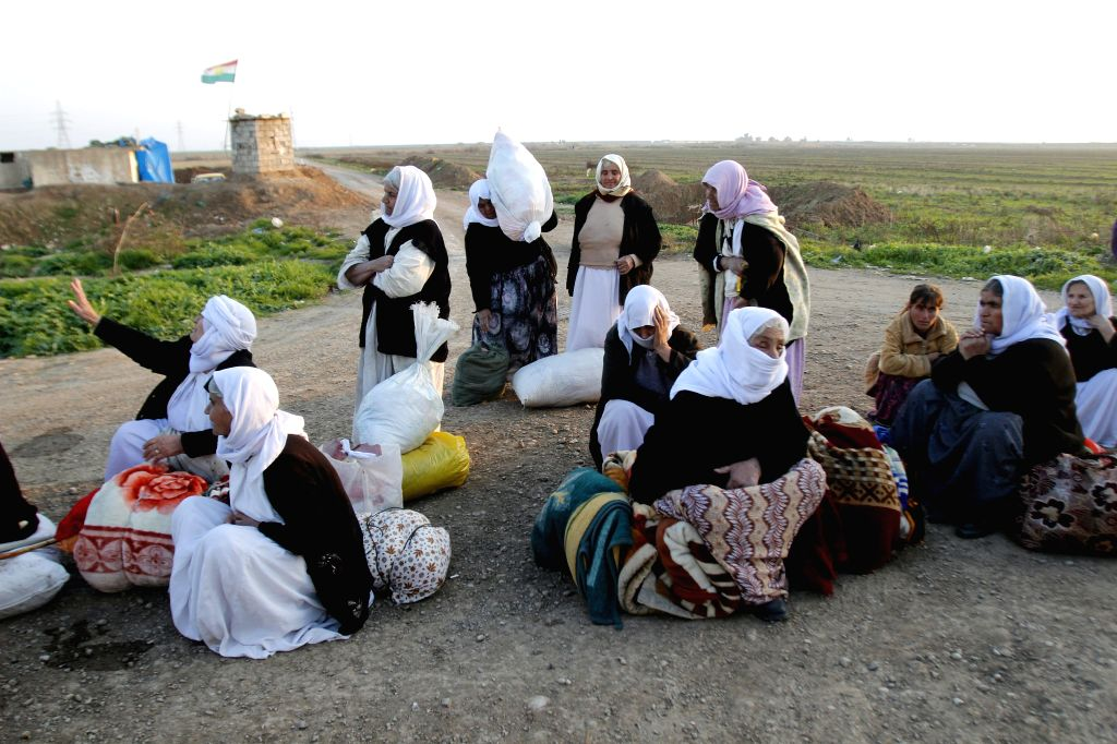 A group of Yazidi women released by Islamic State militants sit on the ground, waiting for assistance in the southwest of Kirkuk, northern Iraq, Jan. 17, 2015. ...