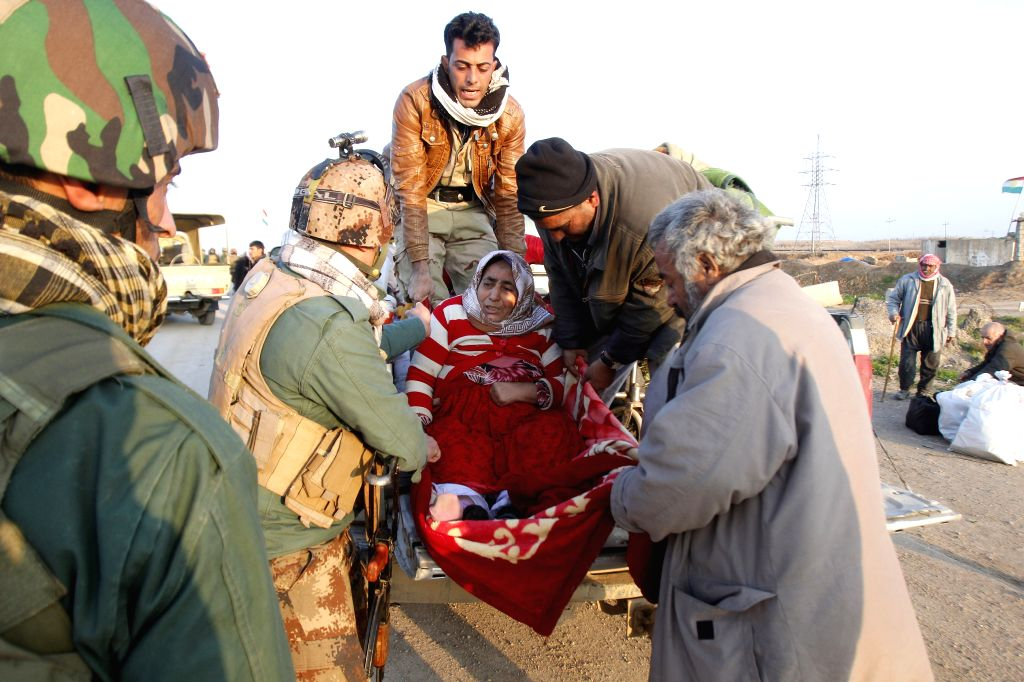 Soldiers of the Kurdish Peshmerga forces assist an old woman who was just released by Islamic State militants in the southwest of Kirkuk, northern Iraq, Jan. 17, ...