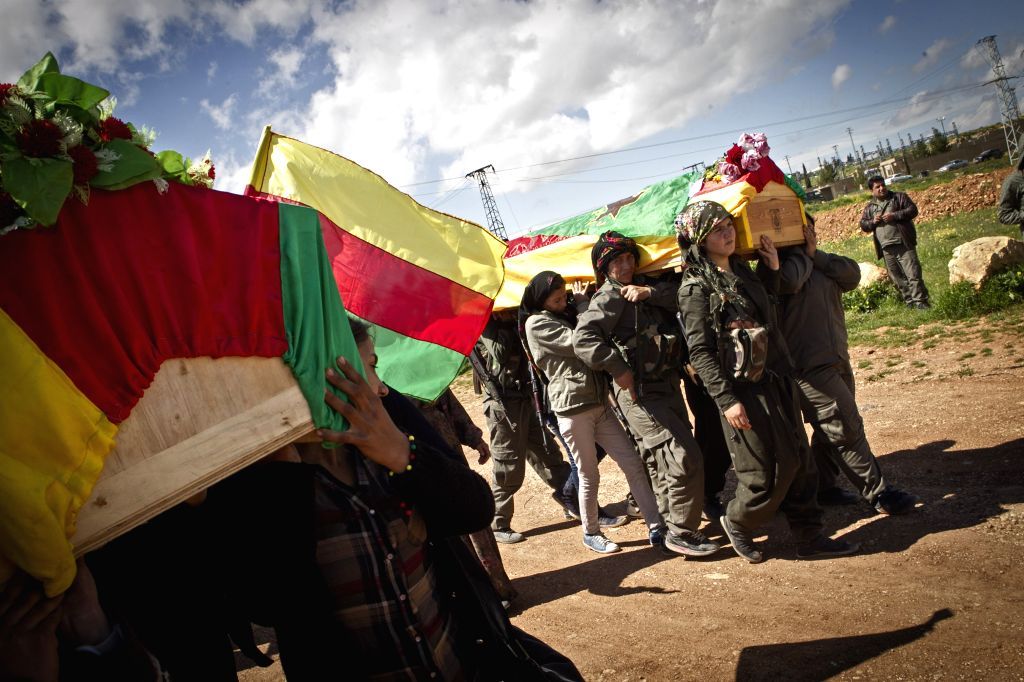 People carry the coffins of Kurdish fighters during a funeral ceremony in Kobane, Syria, on April 2, 2015. Five Kurdish fighters died in clashes with Islamic ...